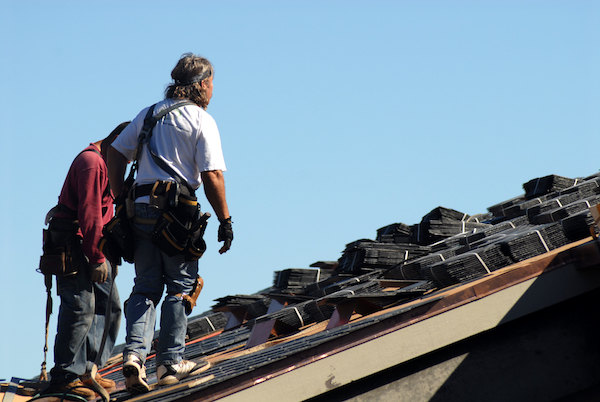 2 roofers with shingle at the top of the roof